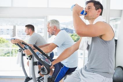 Man on exercise bike drinking water
